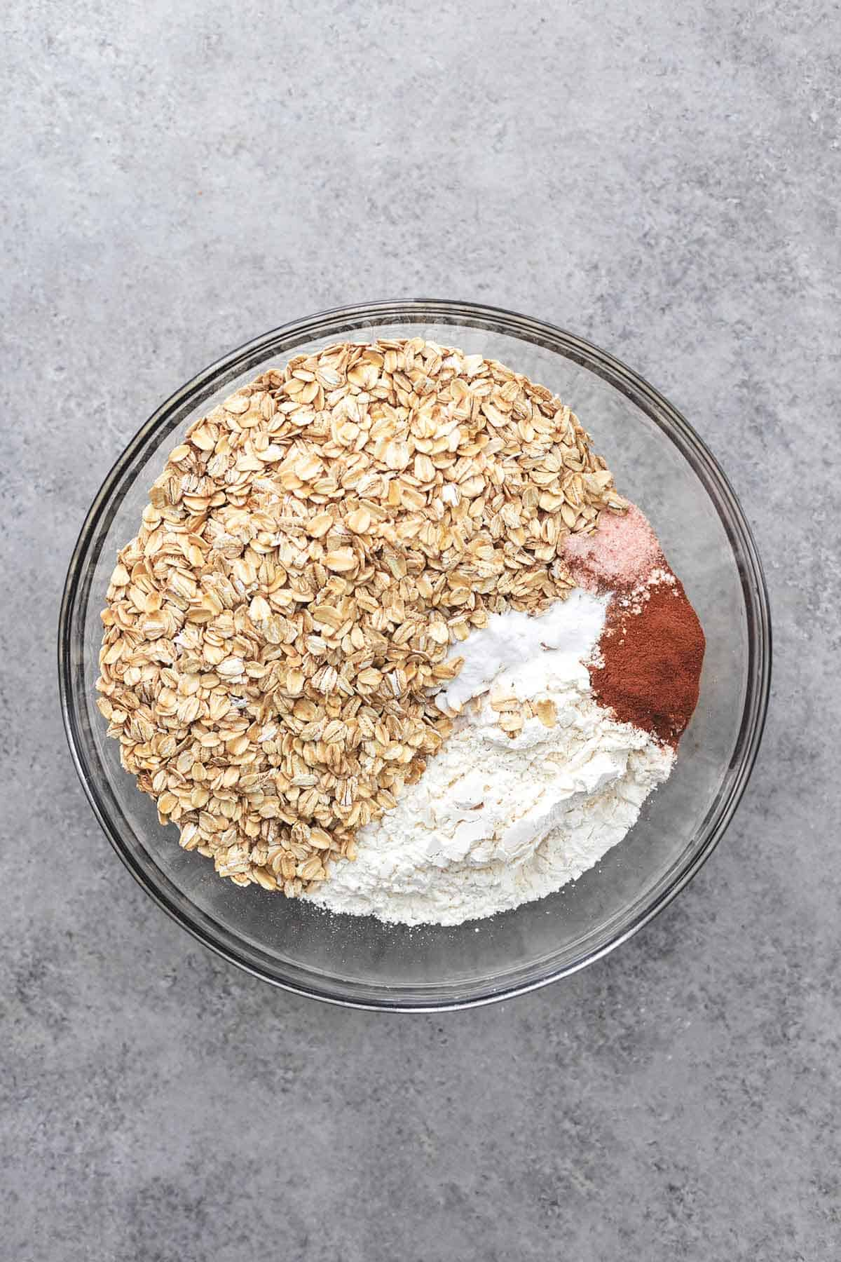 top view of oats, flour, salt, and spices in a glass bowl.