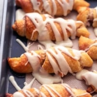 baked cinnamon sugar crescent roll ups with icing on sheet pan