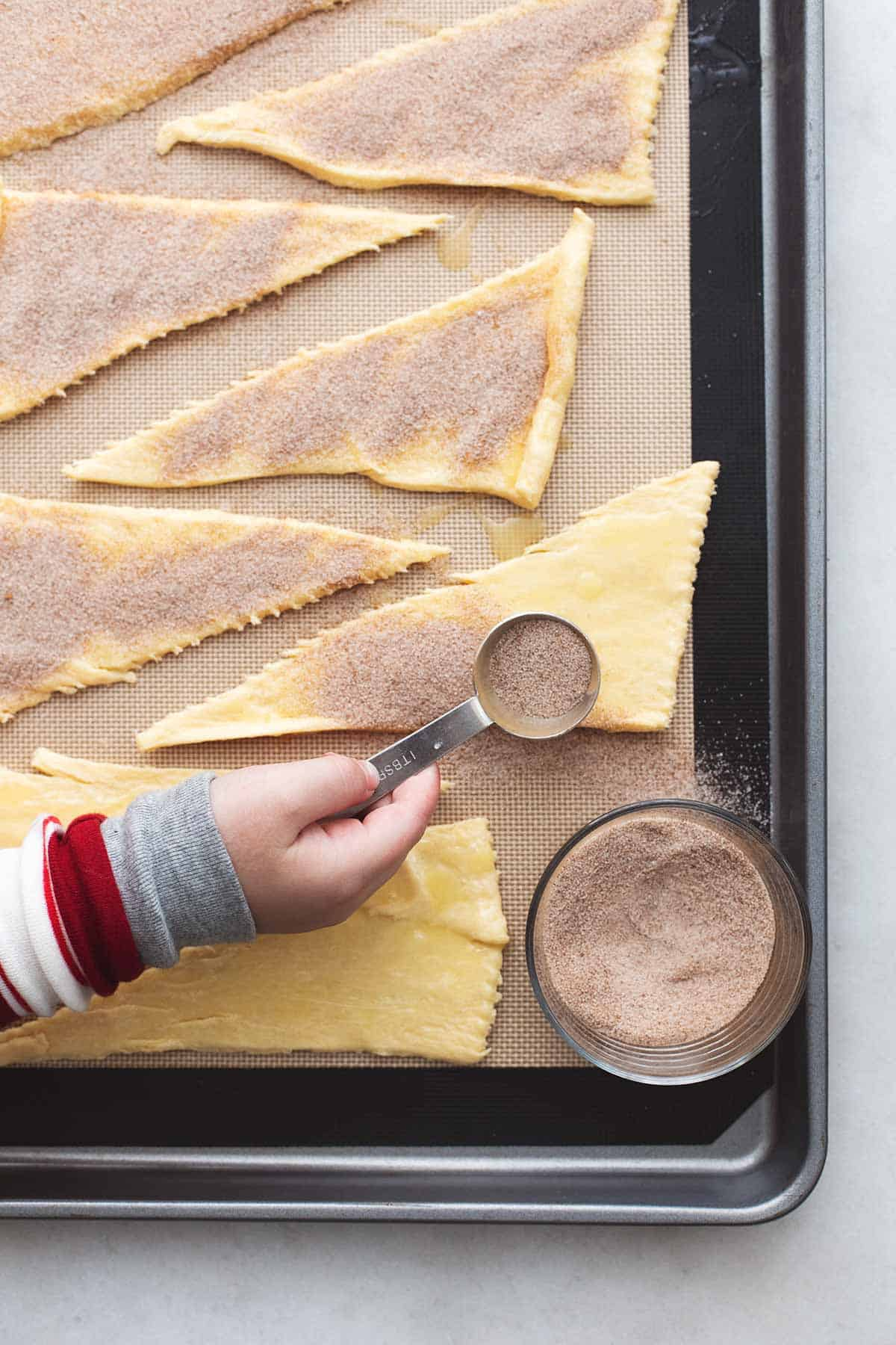 childs hand sprinkling cinnamon and sugar over buttered unbaked crescent triangles