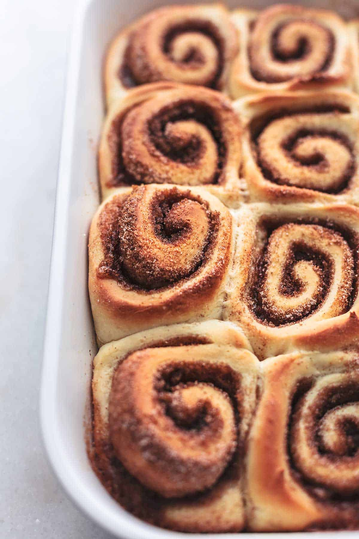 baked cinnamon rolls in white dish without frosting