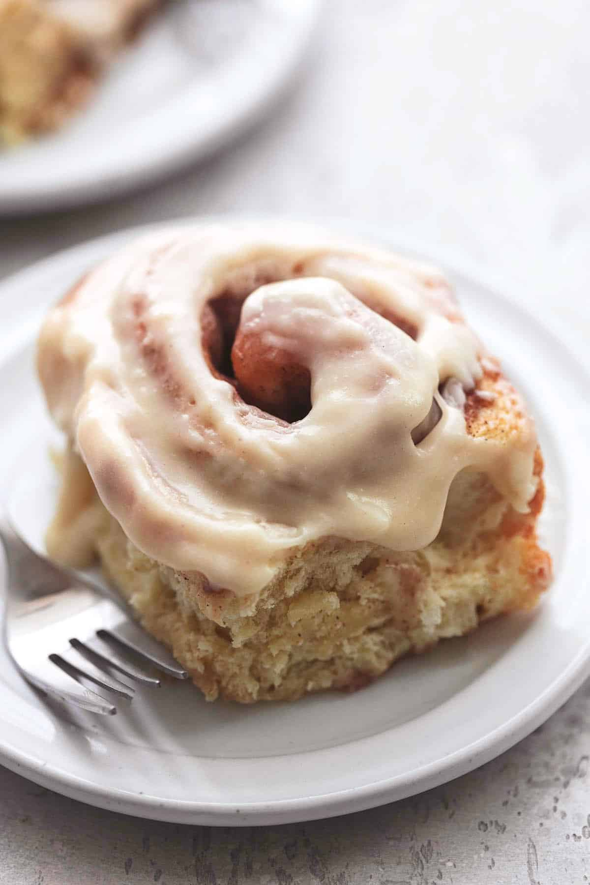 cinnamon roll with white icing on white plate