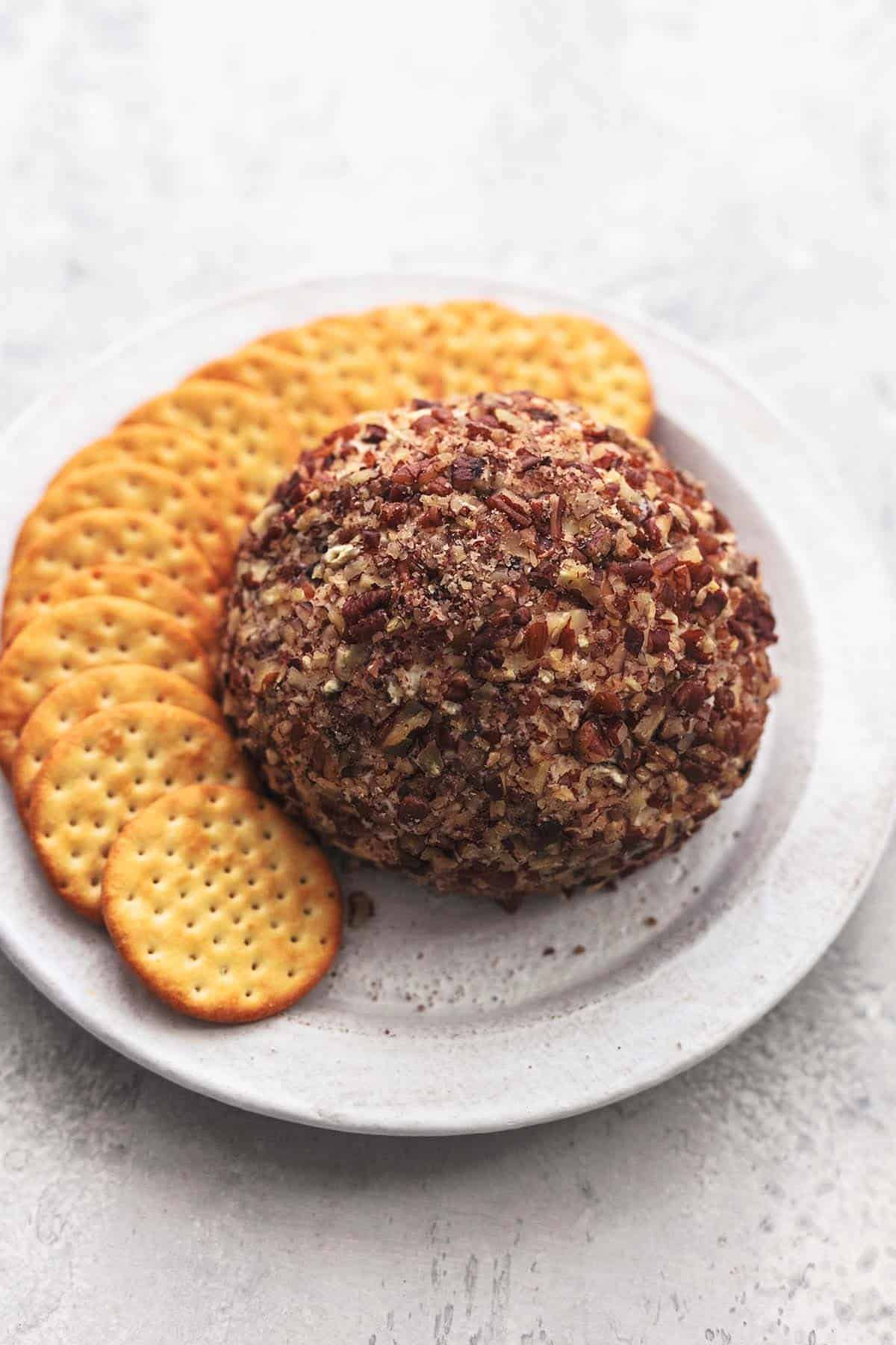 a cranberry pecan cheeseball with crackers on a plate.