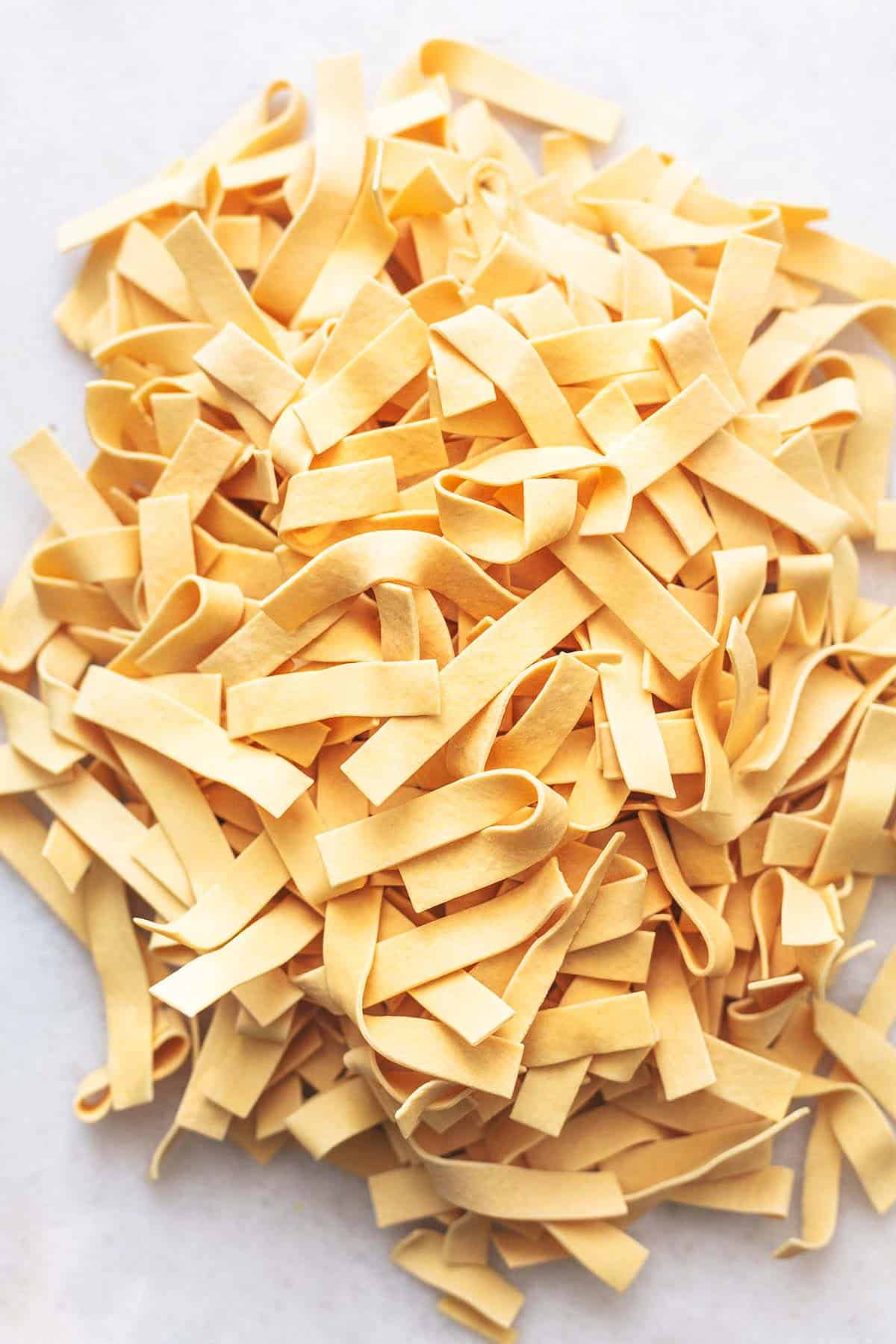 dry egg noodles in a pile on marble tabletop