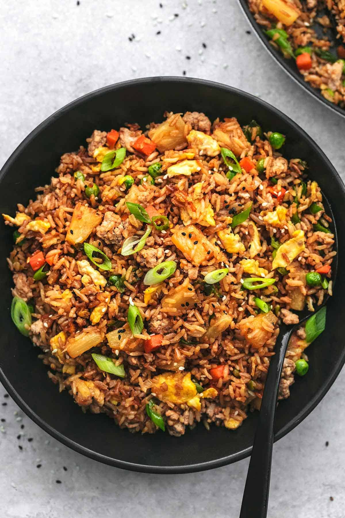 overhead view of rice and veggies with pineapple and pork in black dish
