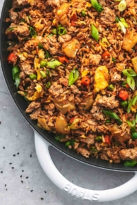 up close quarter of a cast iron skillet filled with asian rice dish