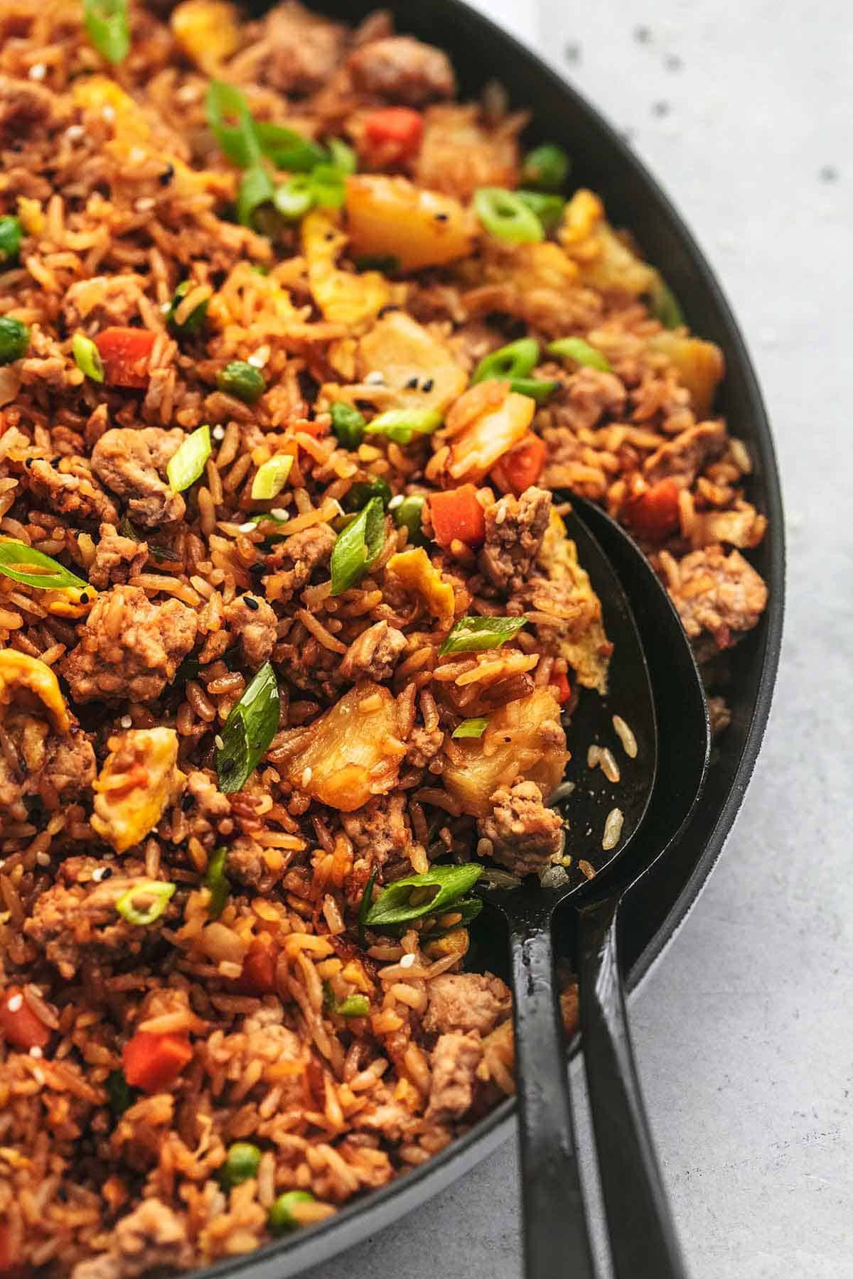 close up of pork fried rice with two serving spoons in a skillet.