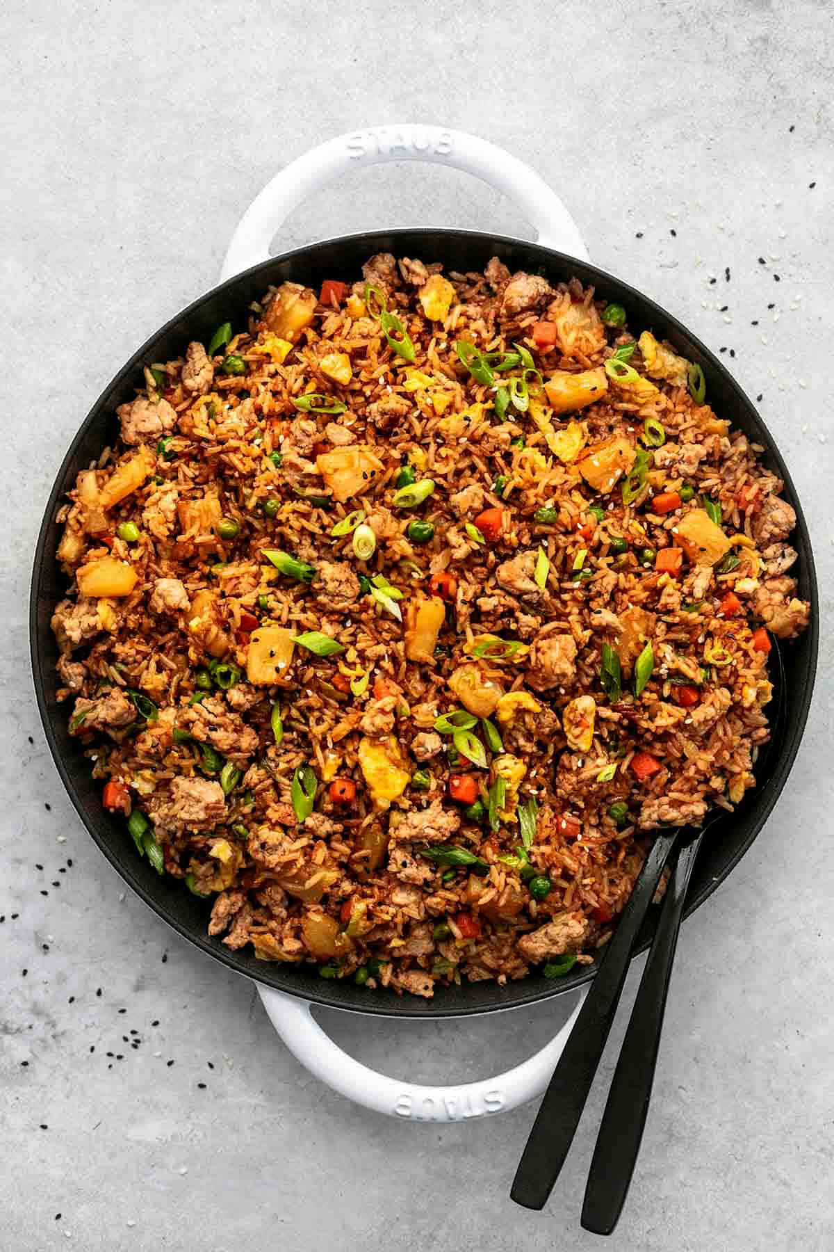 overhead view of pork fried rice with pineapple chunks in a white cast iron skillet