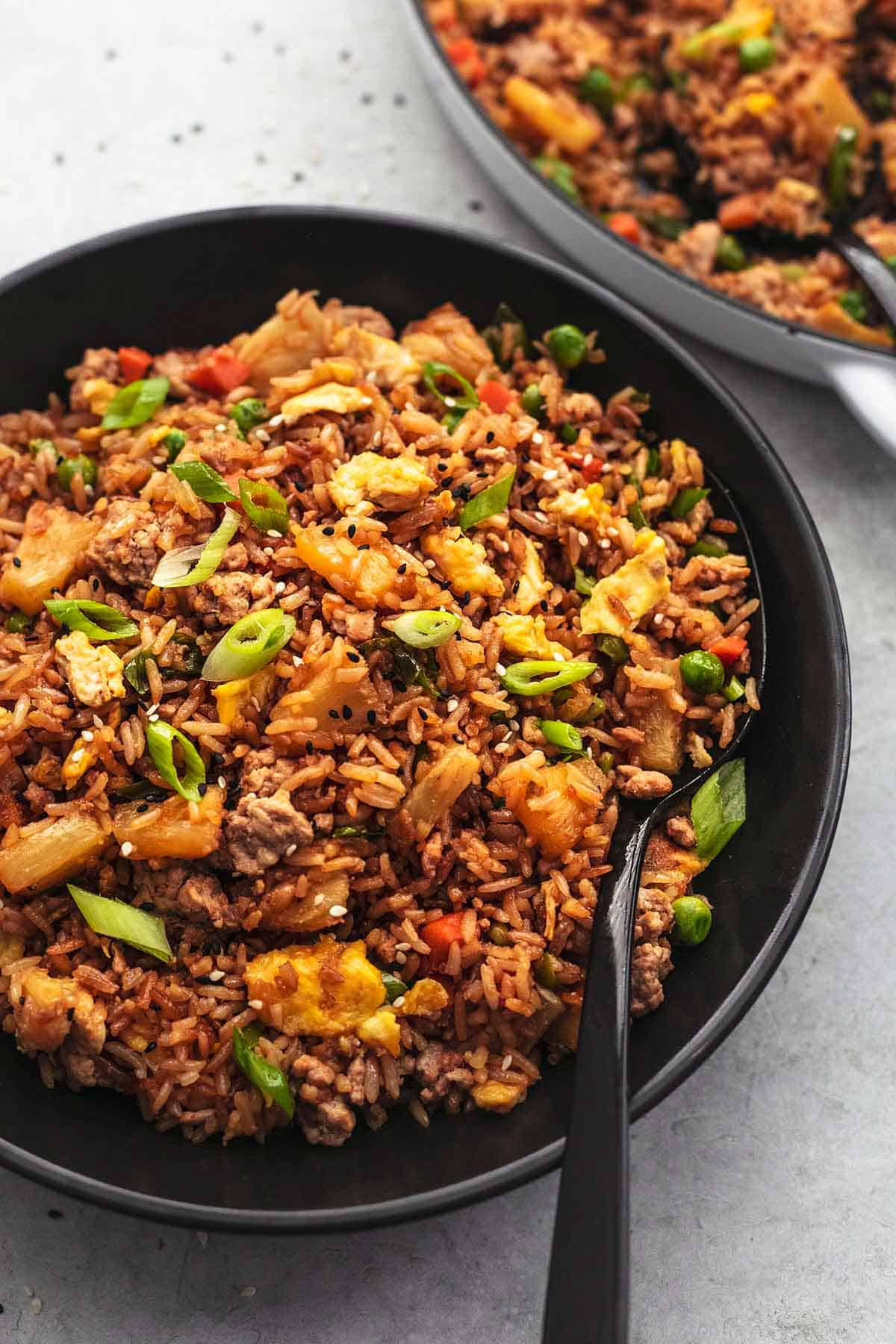 fried rice in black bowl with serving spoon