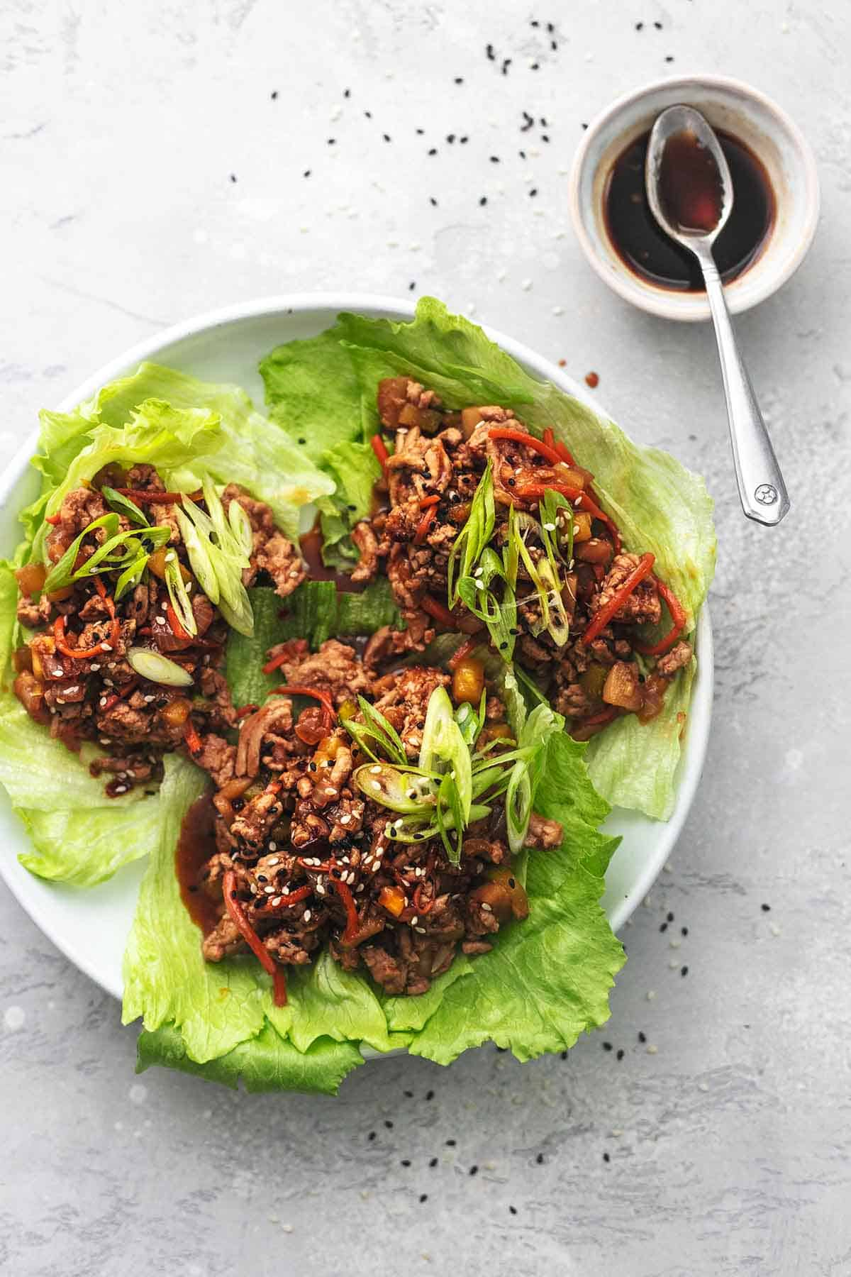 overhead view of three lettuce cups with pork and veggie filling with dark sauce in small bowl