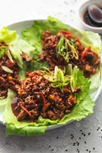 meet and veggies in brown sauce in lettuce cups on plate