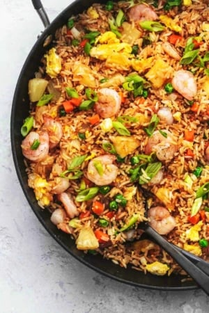 large spoon serving fried rice with vegetables and shrimp