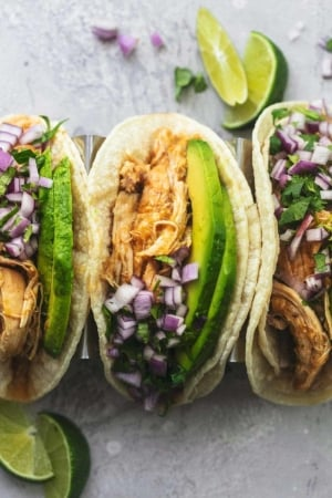 overhead view of three tacos in corn tortillas with shredded chicken and avocado slices