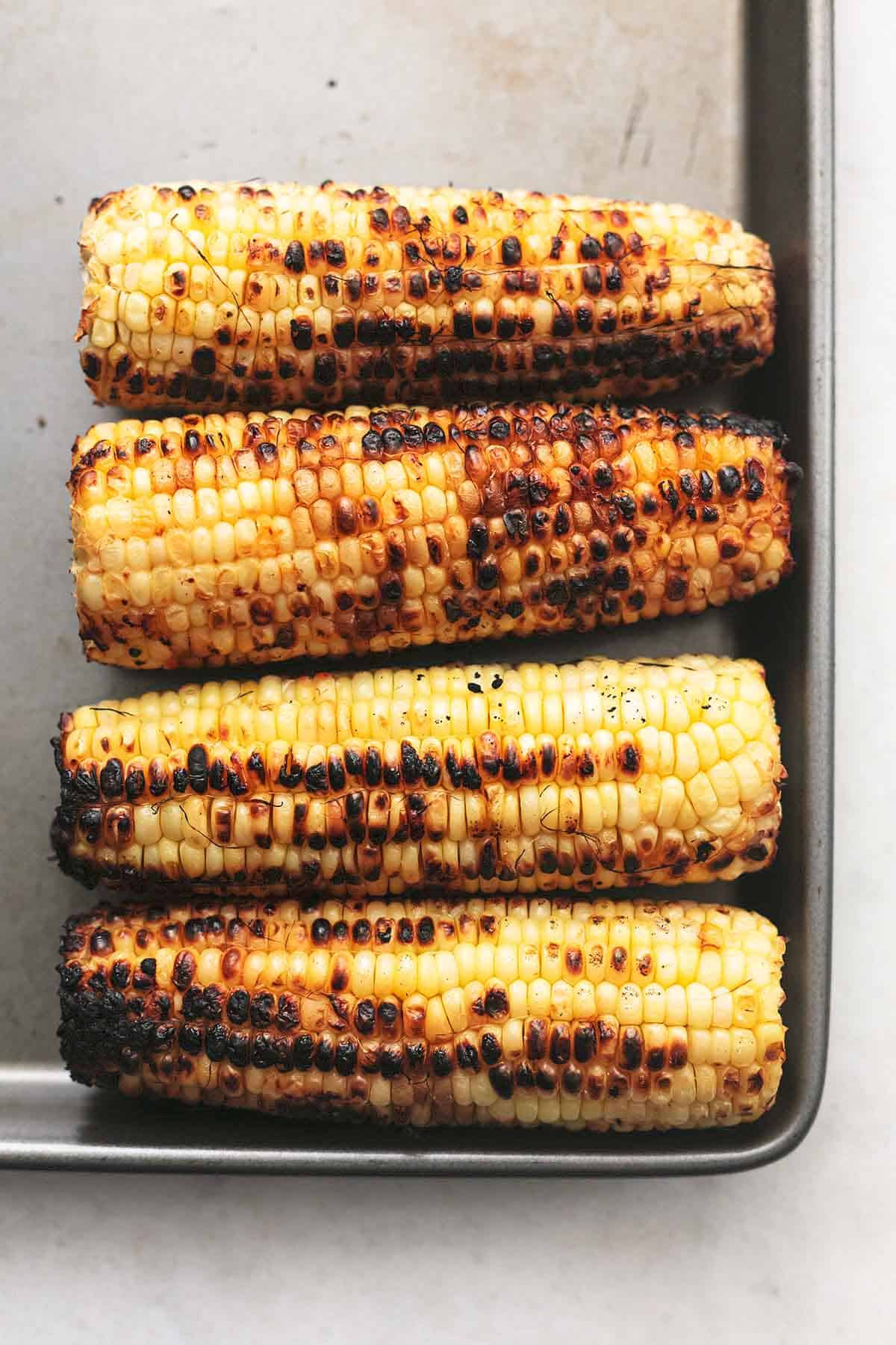 four slightly charred cobs of corn on a gray pan