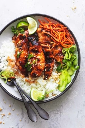 overhead view of plate with grilled chicken, julienned carrots, cucumber ribbons, and lime wedges