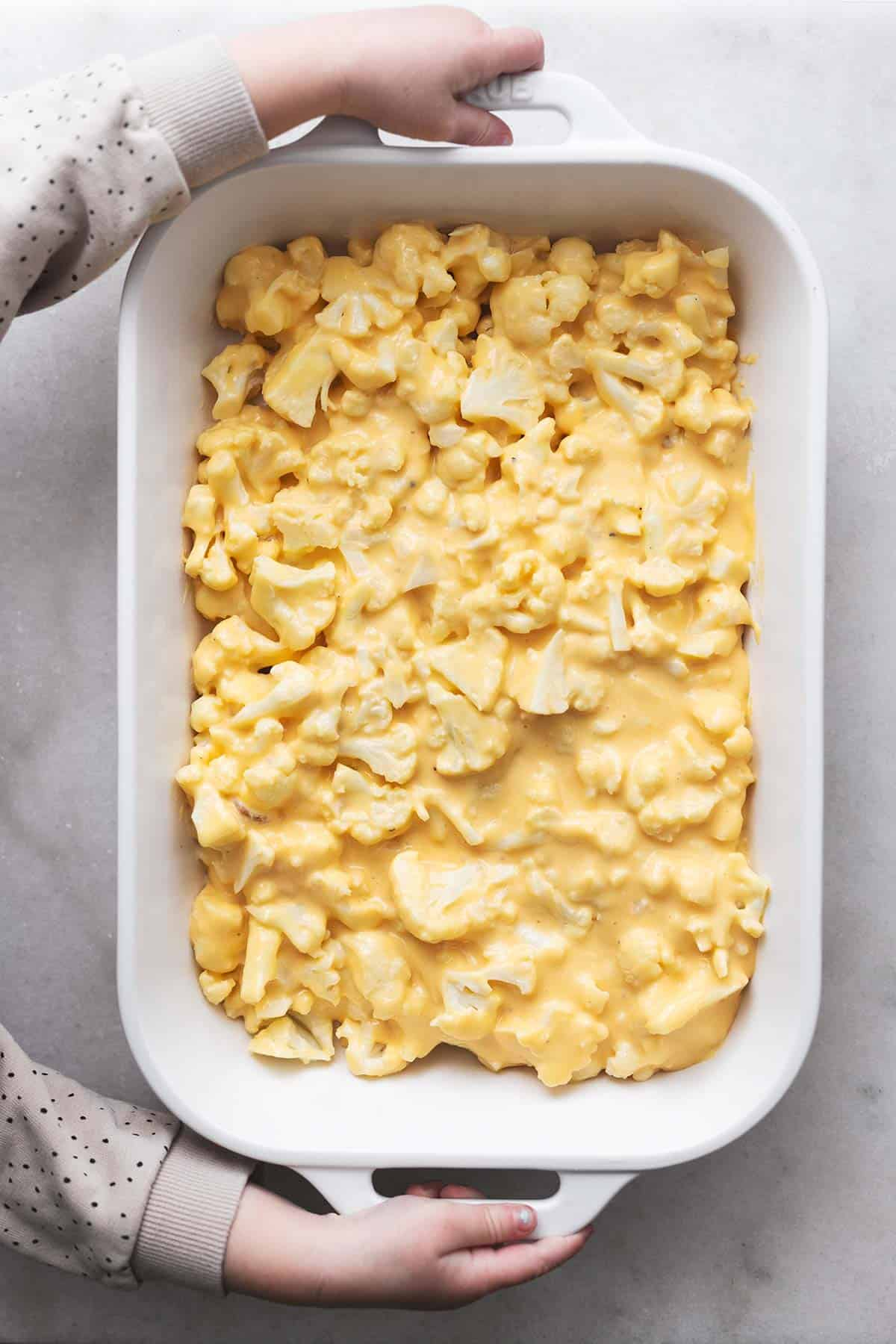 overhead view of hands holding 9x13 white baking dish with cauliflower in cheese sauce