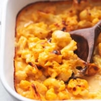 serving spoon with cauliflower mac and cheese in white pan