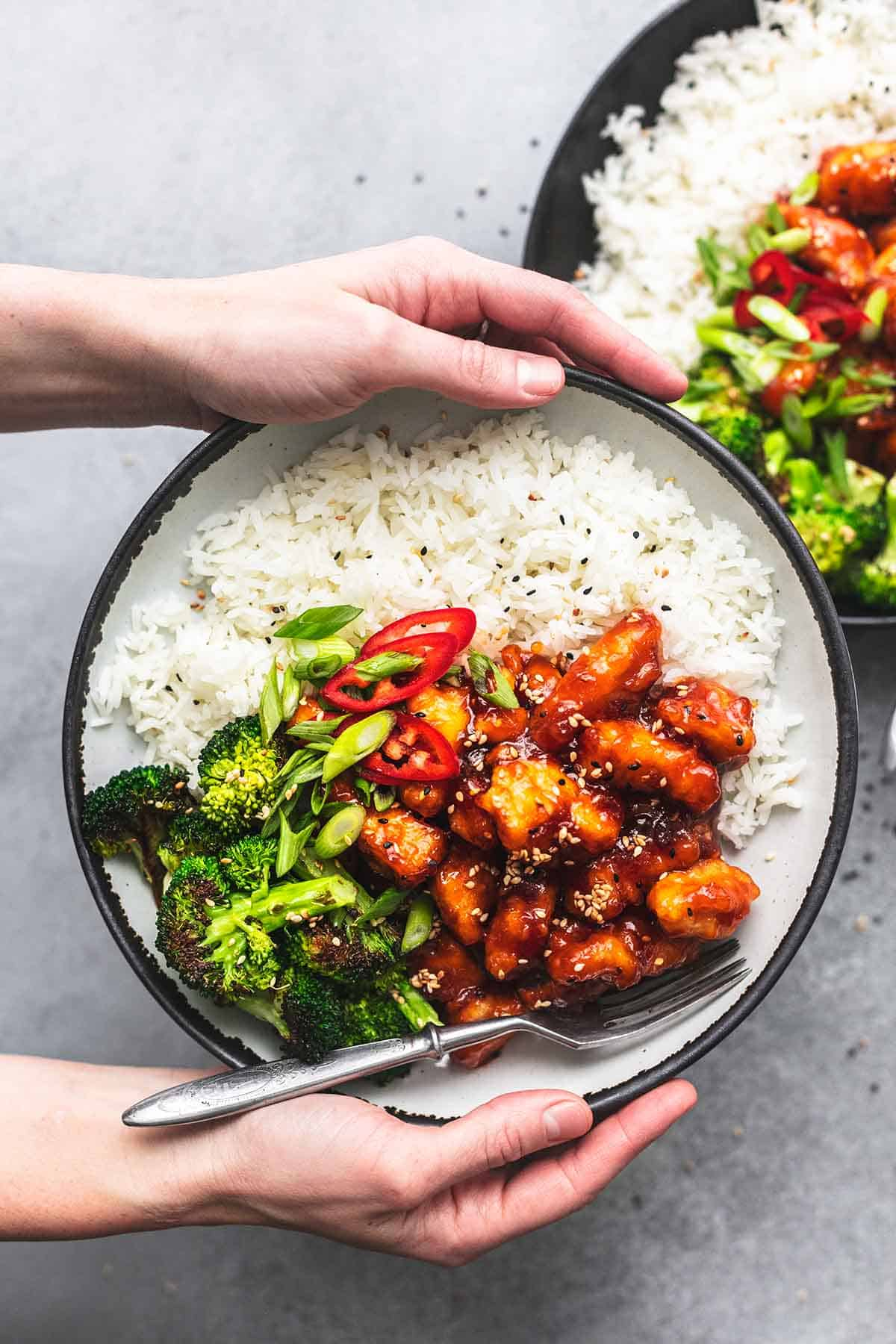 top view of hands holding a plate of sticky sesame chicken with rice and veggies with another plate on the side.