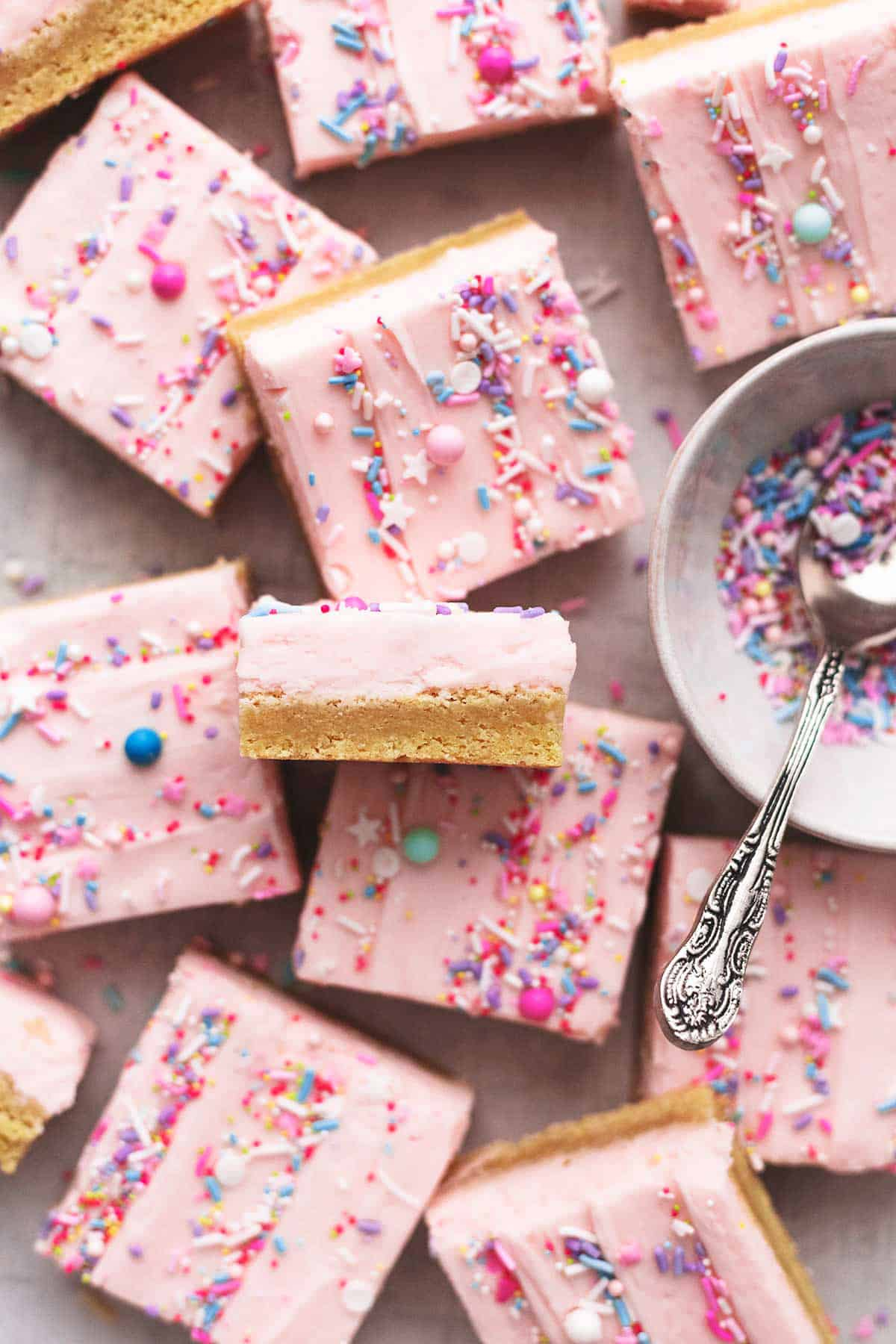 overhead view of sugar cookie bars with pink frosting and sprinkles