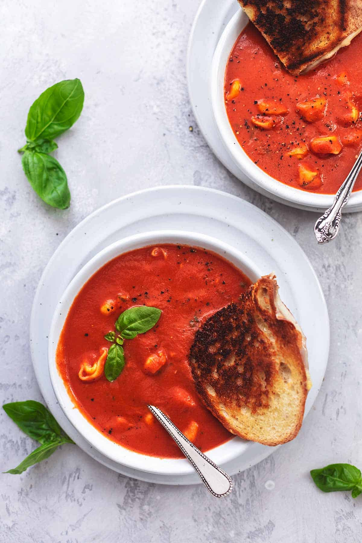 overhead view of two bowls of tomato soup with grilled cheese and basil