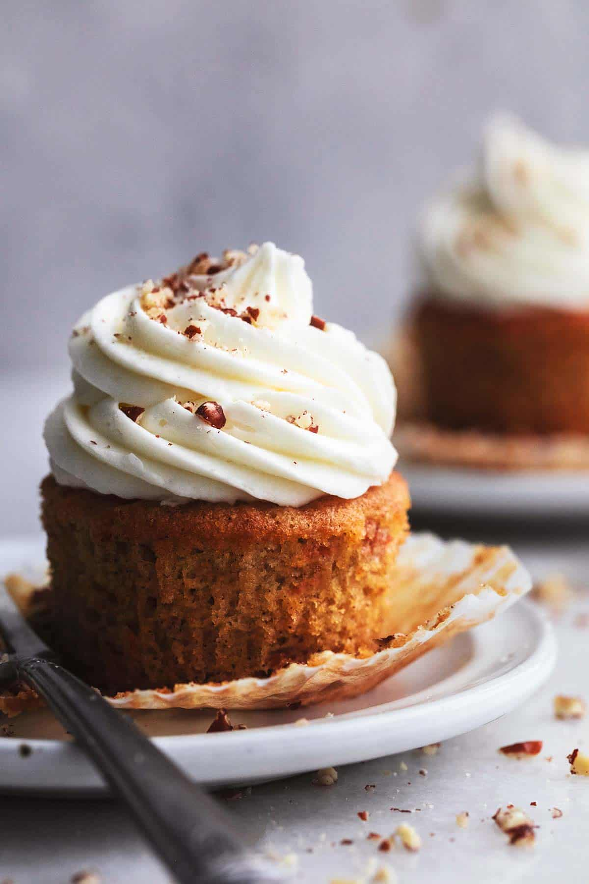 single carrot cupcake unwrapped, on white plate