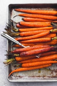 overhead view of roasted whole carrots on sheet pan with fork