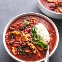 lasagna soup in bowl with spoon, ricotta, and fresh basil garnish