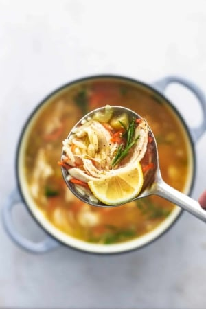 overhead view of ladle full of soup with orzo and chicken and carrots and a lemon wedge