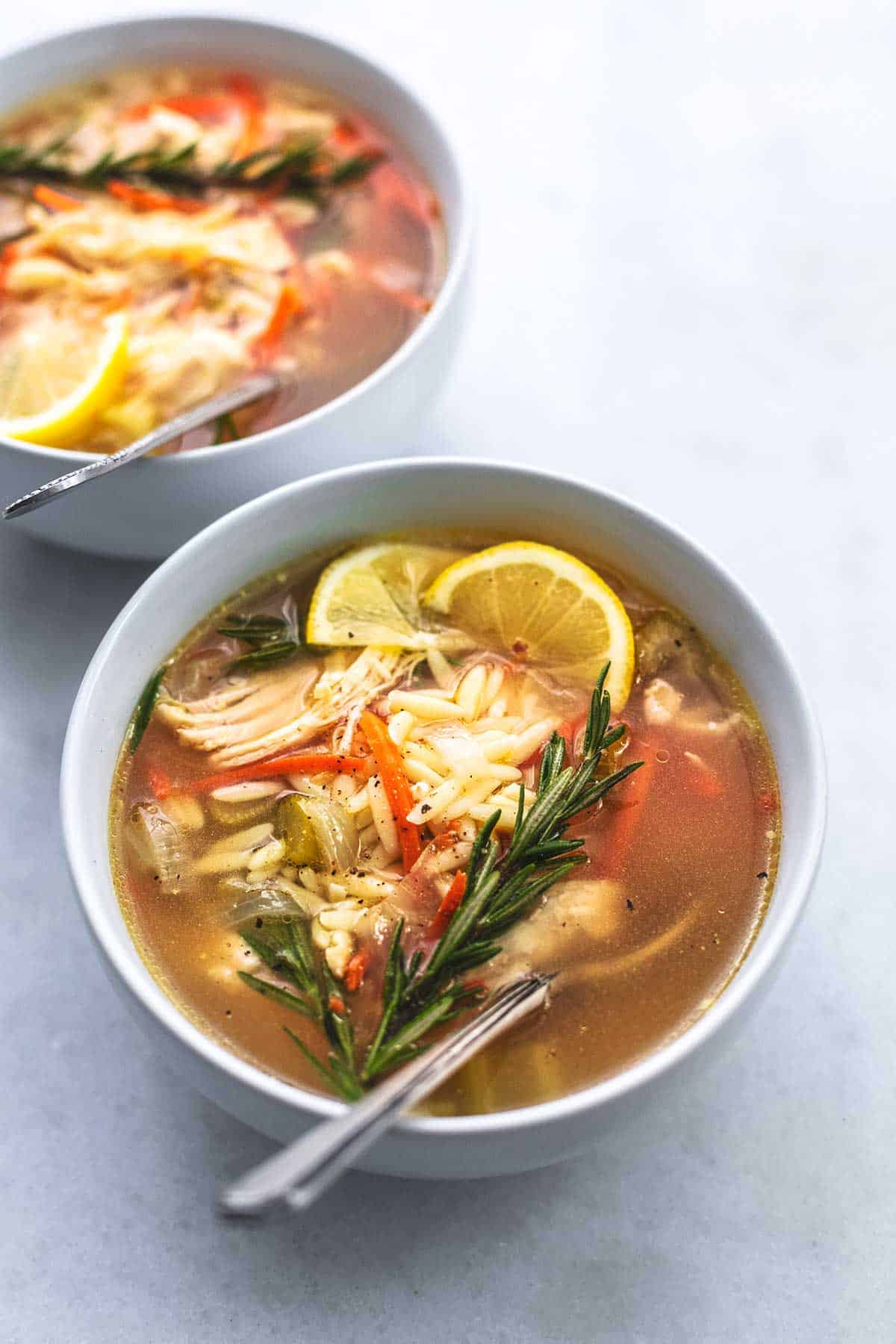 up close bowl of soup with chicken, orzo, lemon wedges, and rosemary sprig