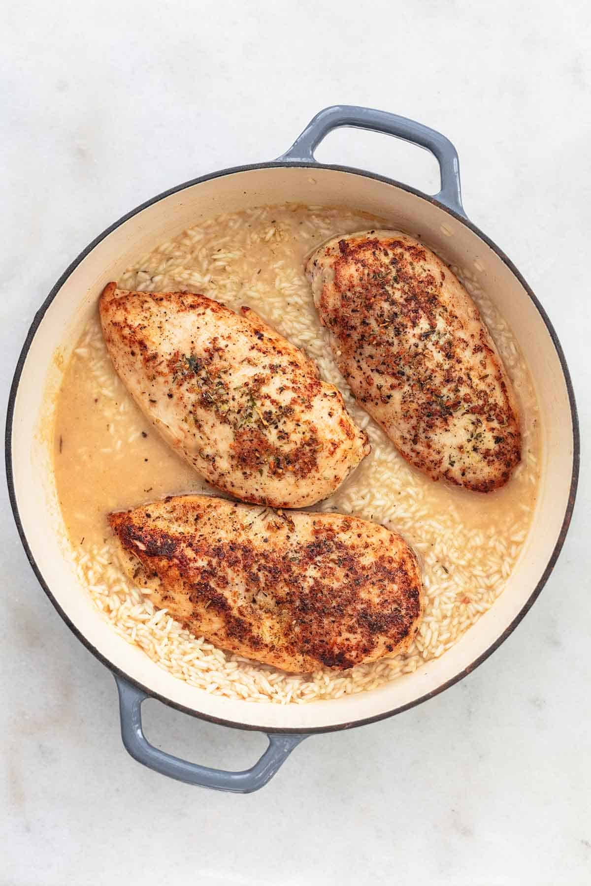 browned chicken breasts and uncooked rice in liquid in skillet
