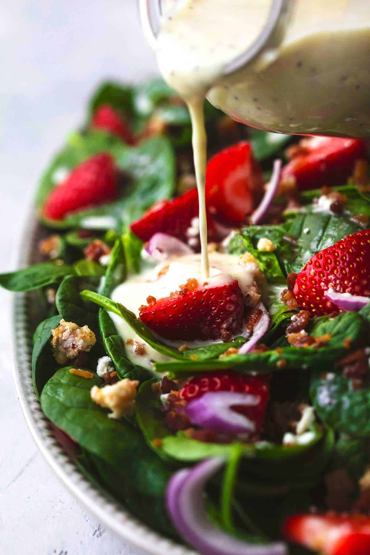 up close view of creamy white salad dressing being poured onto strawberries in spinach salad with red onions and bacon crumbles