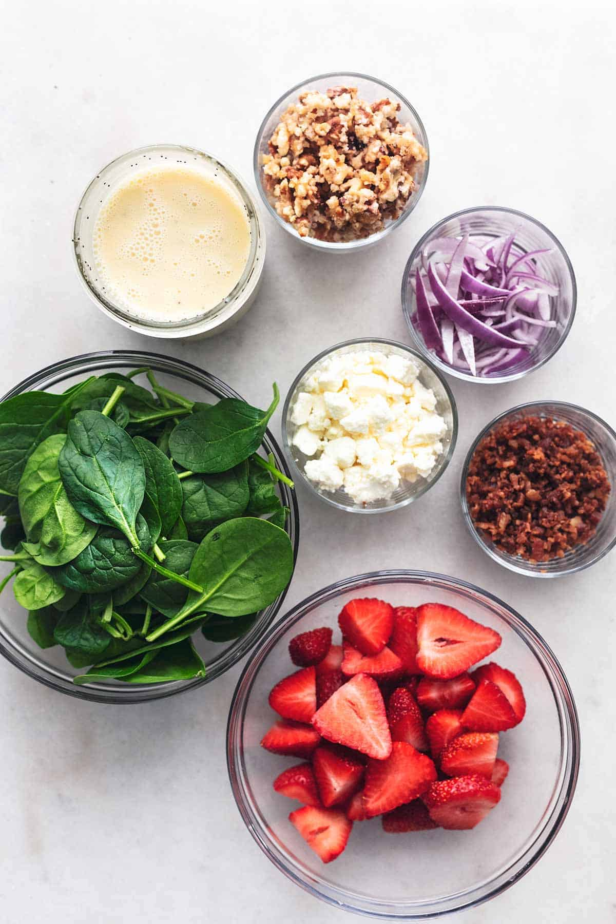 overhead view of ingredients for spinach salad with strawberries and bacon on marble tabletop