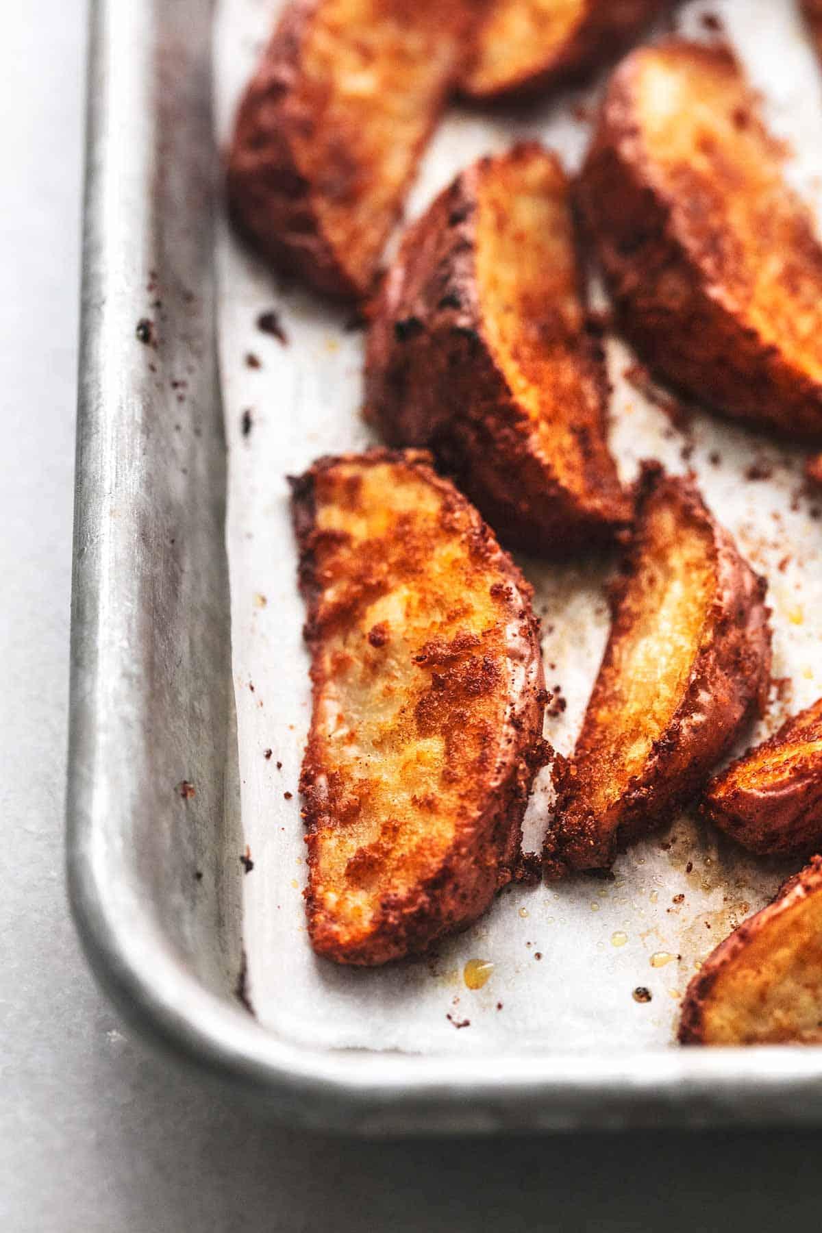 close up view of several seasoned potato wedges on baking sheet