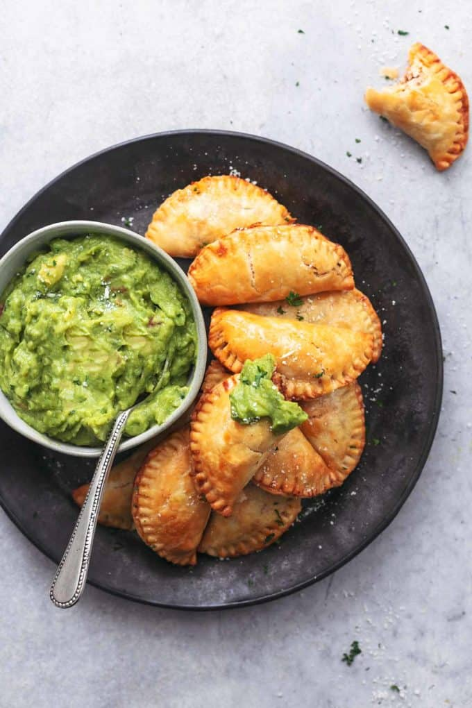overhead view of empanadas and guacamole on plate