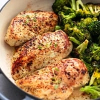 three seasoned, cooked chicken breasts in skillet beside broccoli