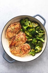 overhead view of three cooked chicken breasts with cooked broccoli in skillet