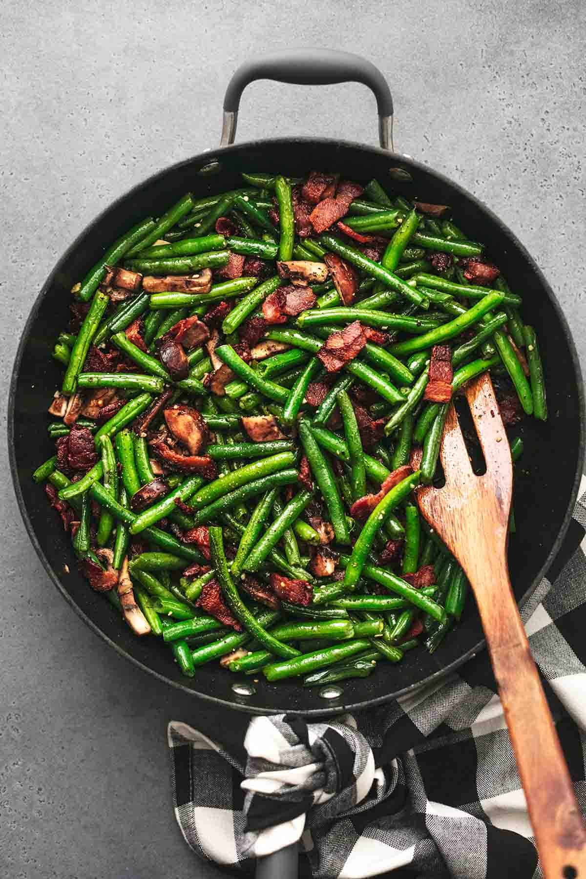 top view of green beans with mushrooms and bacon with a wooden spatula in a skillet.