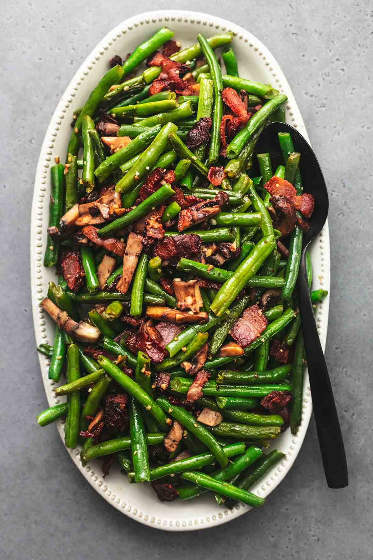 top view of green beans with mushrooms and bacon with a serving spoon on a platter.