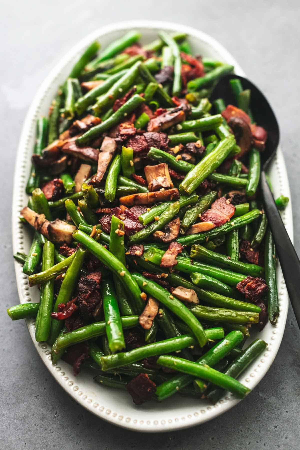 coclose up of green beans with mushrooms and bacon with a serving spoon on a platter.