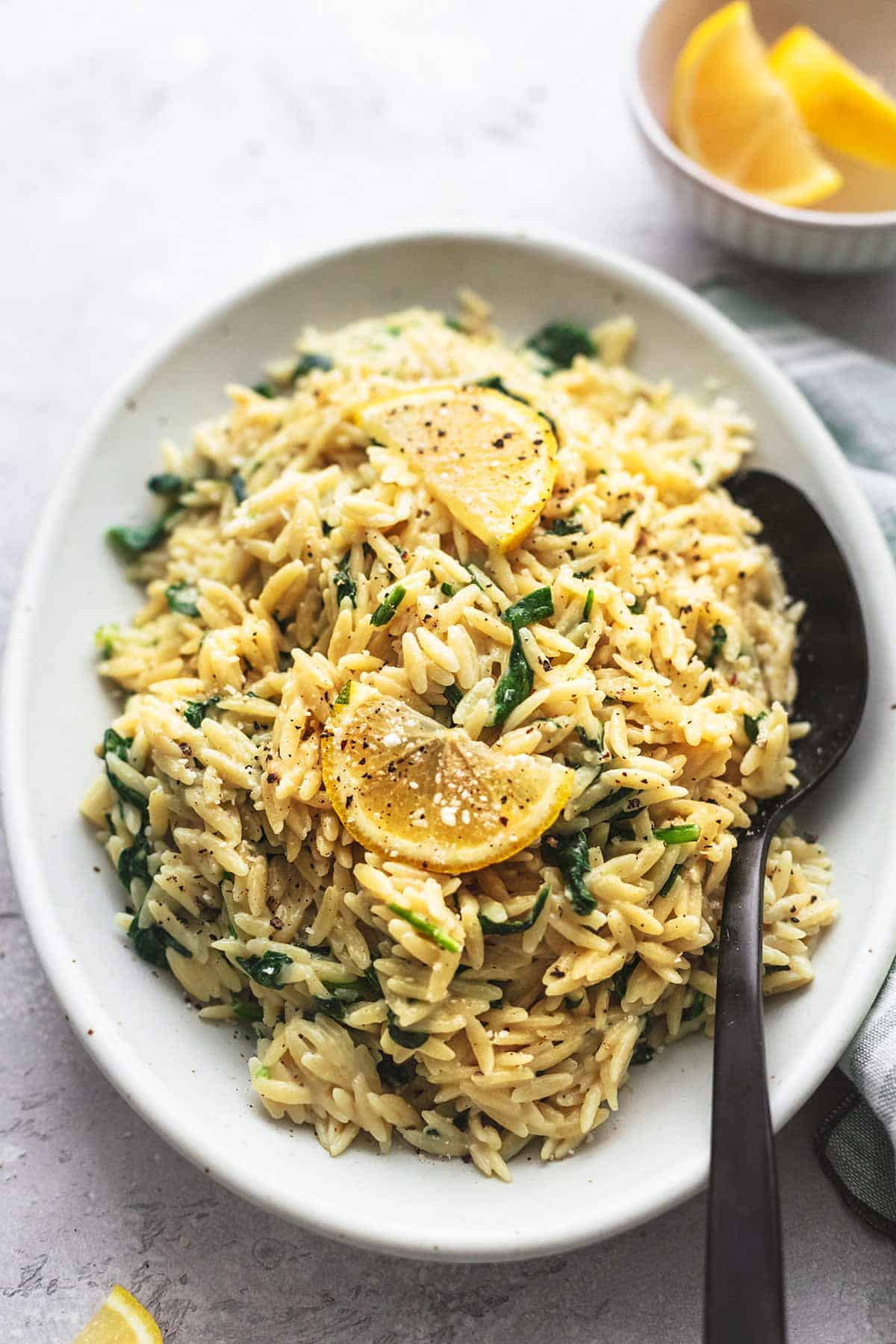 creamy parmesan spinach orzo with a serving spoon on a platter.
