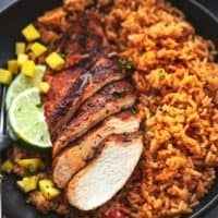 cajun chicken breast sliced with lime wedges and diced mangoes with rice on plate
