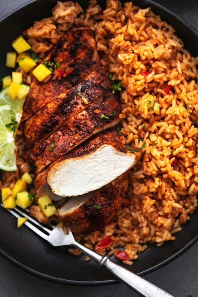 sliced cajun chicken breast with rice and mangoes with fork