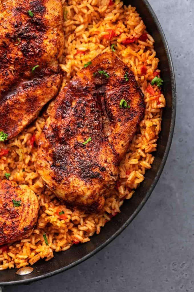 blackened seasoned chicken on top of seasoned rice in skillet