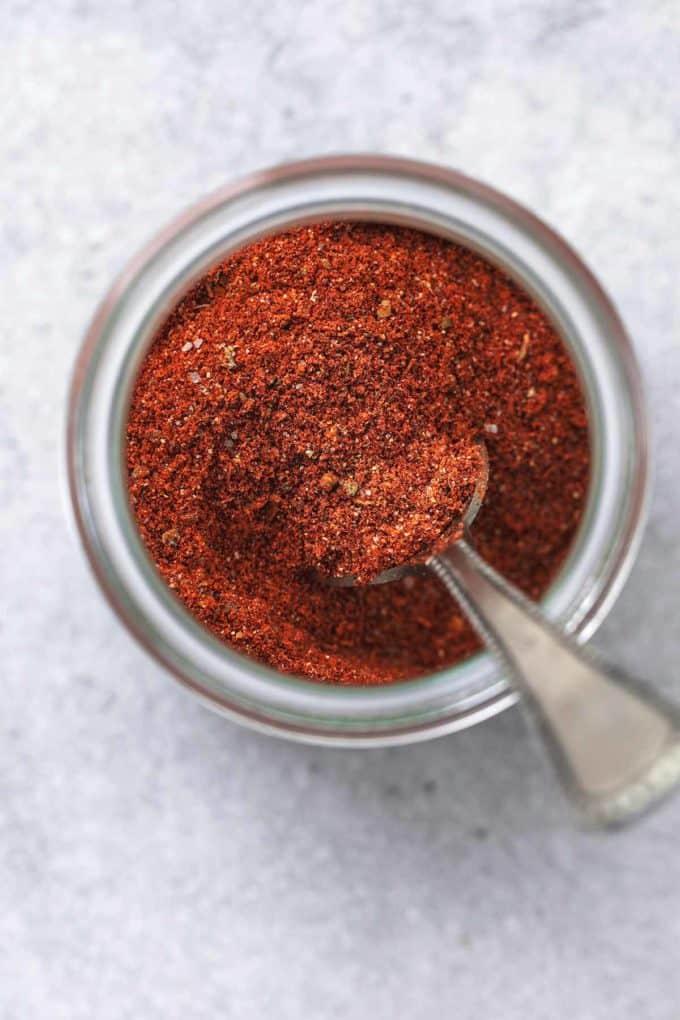 jar of cajun seasoning with spoon in jar
