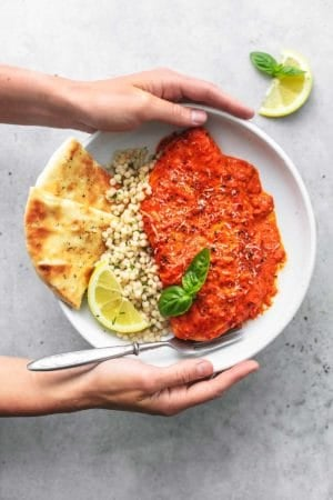 overhead view of hands holding plate of couscous with chicken and pita bread