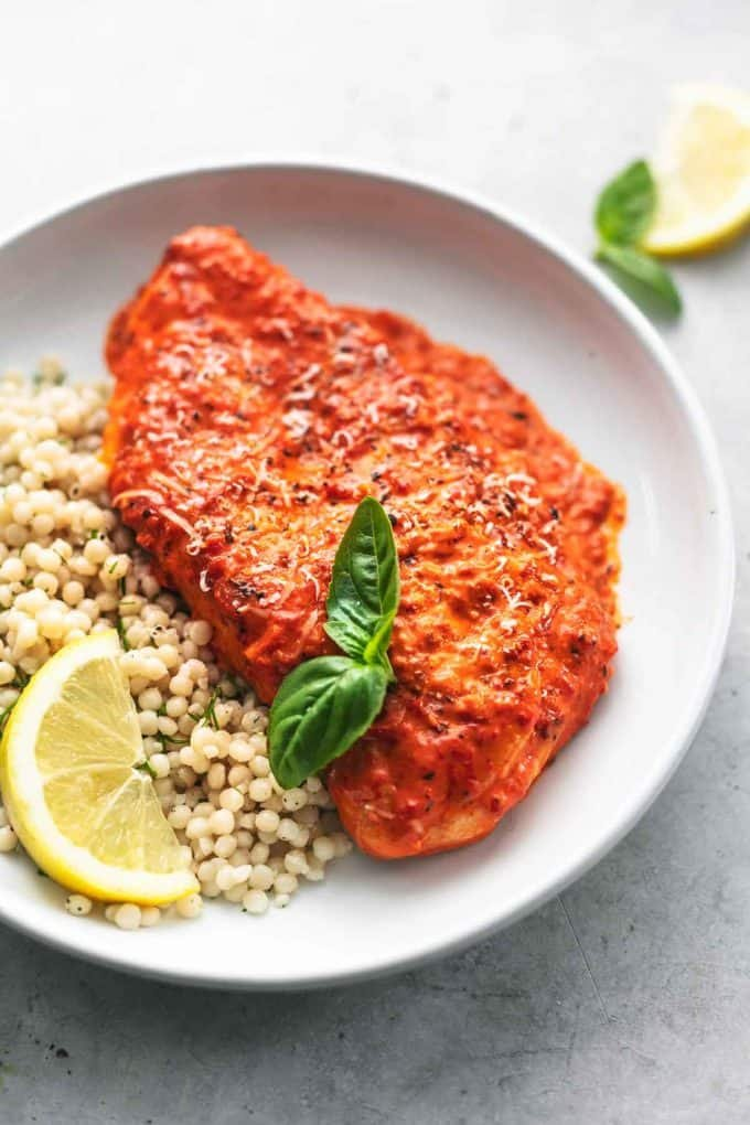 single chicken breast in sauce with fresh basil, lemon wedge, and couscous on plate
