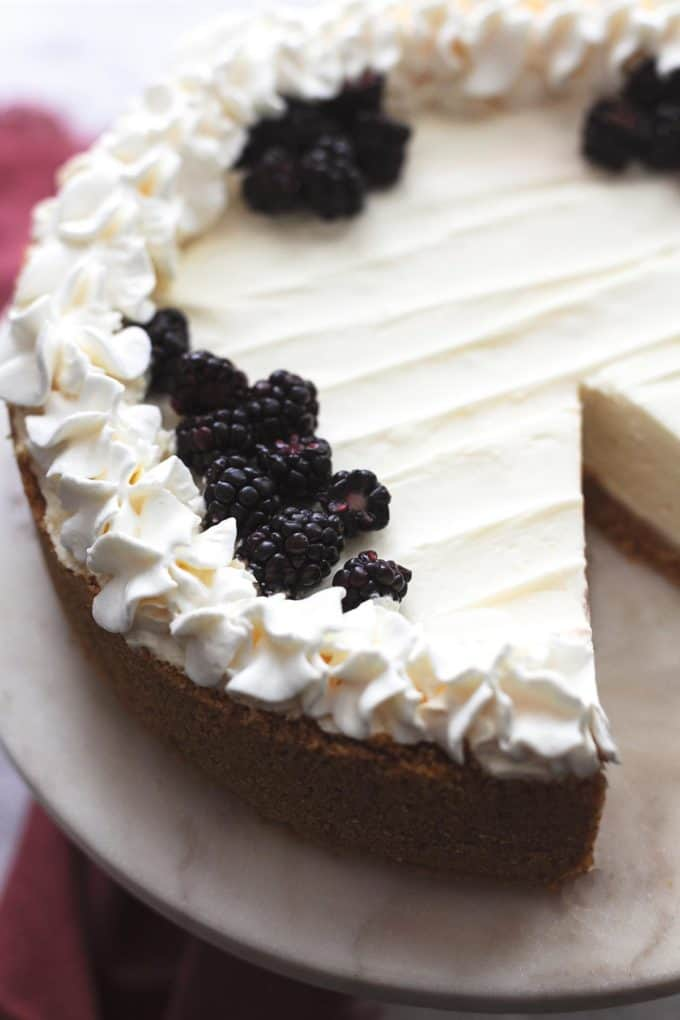 three quarters of a plain white cheesecake with whipped cream and graham cracker crust