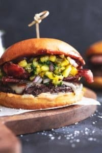 hamburger with bacon, cheese, and pineapple relish on wood cutting board