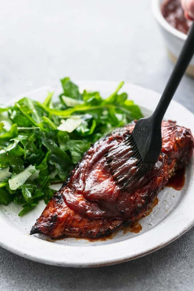 basting brush spreading bbq sauce onto grilled chicken breast