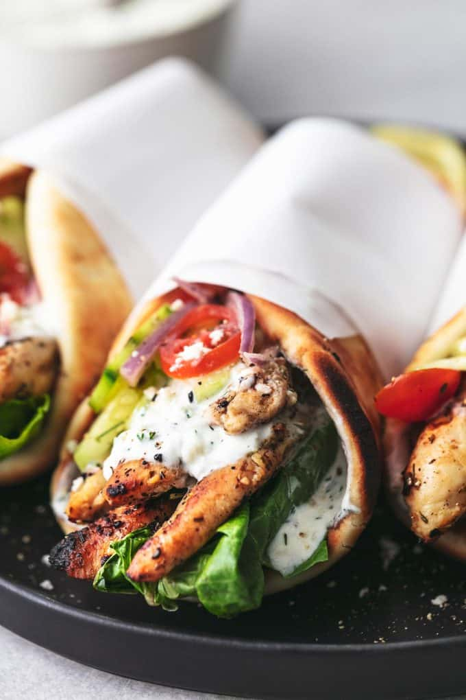 chicken gyro on a plate with paper wrapped around pita bread