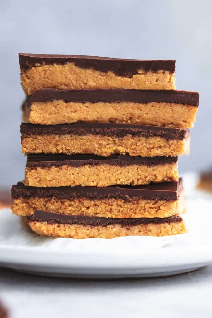 stack of peanut butter bars on top of cupcake liner on top of plate